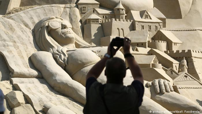 A man in silhouette takes a photo of the 2016 sandcastle record attempt in Duisburg