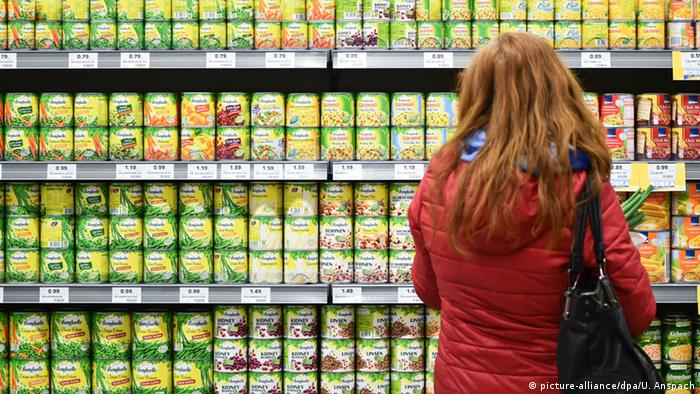 A woman looking at canned products in a supermarket (picture-alliance/dpa/U. Anspach)