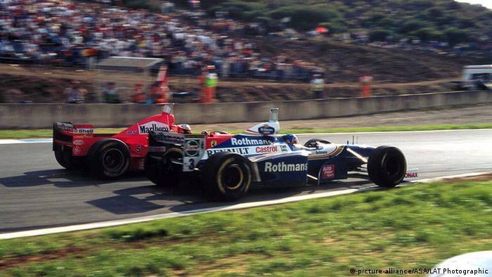 Carro vermelho de Michael Schumacher, ao fundo, bate no de Jacques Villeneuve (azul e branco) no GP Europa de 1997, pouco antes de curva
