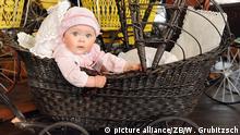 Дитина сидить в одному з найстаріших візків