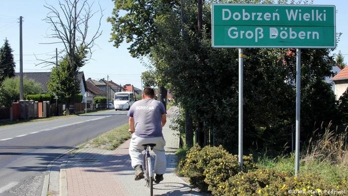 A man rides a bike passed a signpost for the town of Dobrzeń Wielki