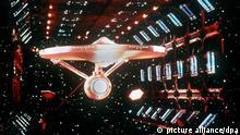 Das Flaggschiff der Serie, die USS Enterprise. Aus der Anfang der 60er Jahre gestarteten US-Fernsehserie Star Trek, die in Deutschland unter dem Titel Raumschiff Enterprise läuft, wurde weltweit echter Kult: Trekkies finden sich zu Treffen zusammen und fachsimpeln über die Weltraumabenteuer von Captain James T. Kirk und seiner Crew. | Verwendung weltweit picture alliance/dpa