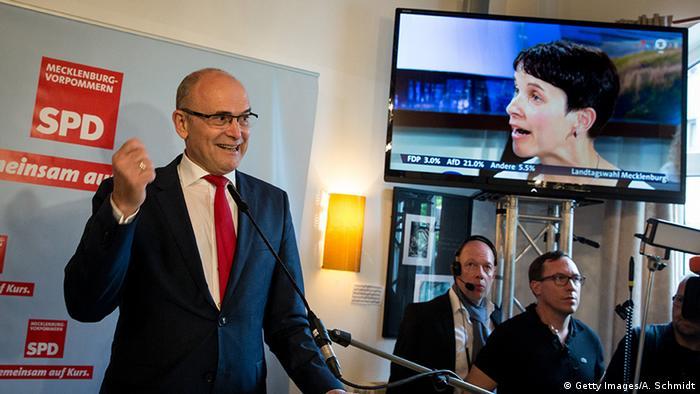 Действующий глава Мекленбурга - Передней Померании Эрвин Зеллеринг от СДПГ на фоне кадра ТВ с изображением лидера АдГ Фрауке Петри