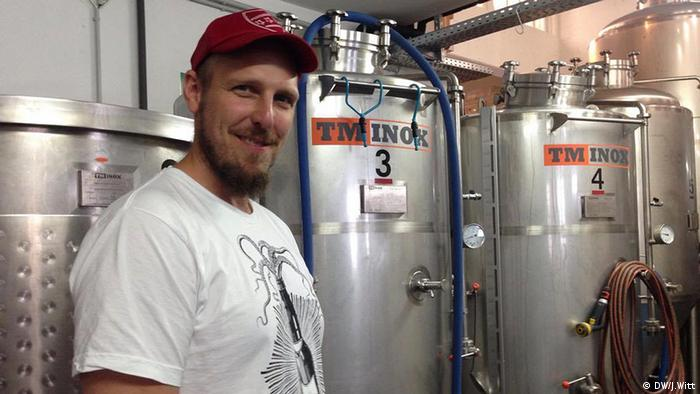 Simon Siemsglüss of Buddelship Brewery poses for a photo in front of a row of metal kegs