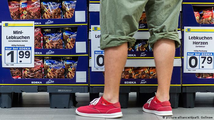 A man wearing shorts in a supermarket in front of a row of Lebkuchen (picture-alliance/dpa/S. Gollnow)