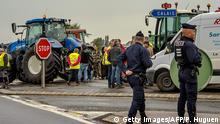 05.09.2016 *** French police officers stand guard as French farmers gather at Marck prior to meet with a dozen of truck drivers on September 5, 2016 for a slow-down operation on the A16 highway to ask for the dismantling of the so-called 'Jungle' migrant camp in the French northern port city of Calais. / AFP / PHILIPPE HUGUEN (Photo credit should read PHILIPPE HUGUEN/AFP/Getty Images) © Getty Images/AFP/P. Huguen