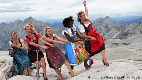 Women dressed in dirndl climbing atop the Zugspitze (picture-alliance/dpa/F. Hörhager)