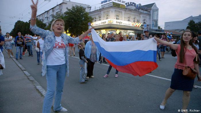 Frauen mit einer russischen Flagge freuen sich über den Anschluss der Krim an Russland.