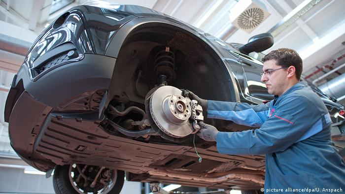 Car worker fitting a wheel (picture alliance/dpa/U. Anspach)