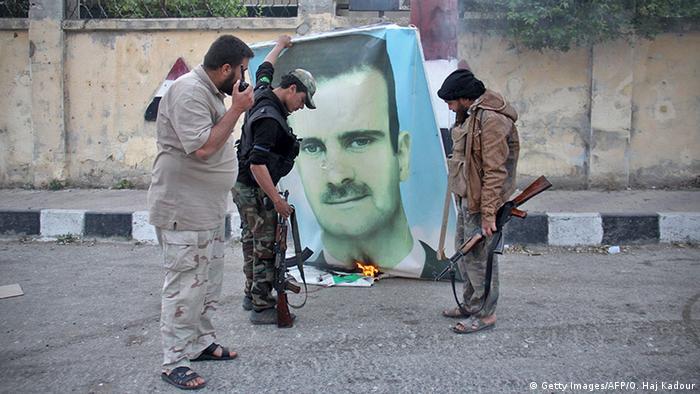 Повстанцы в сирийском городе Идлиб сжигают портрет Башара Асада