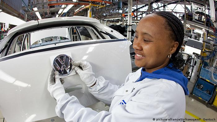 A female Volkswagen worker in South Africa putting the VW sign on a new Polo car (picture-alliance/Volkswagen/F. Gentsch)