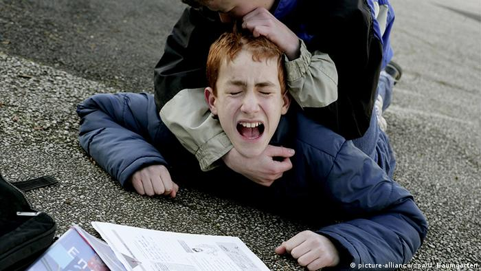 A child in an acted-out scene is bullied by another child (picture-alliance/dpa/U. Baumgarten)