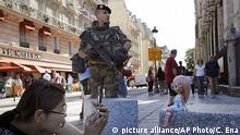 Sept. 9, 2016**** A French soldier stands guard as a tourist takes pictures of her doll in front of Notre Dame cathedral, in Paris, Friday Sept. 9, 2016. A failed attack involving a car loaded with gas canisters near Notre Dame Cathedral was spearheaded a group of women that included a 19-year-old whose written pledge of allegiance to the Islamic State group was found by police, a security official said Friday. (AP Photo/Christophe Ena) | picture alliance/AP Photo/C. Ena