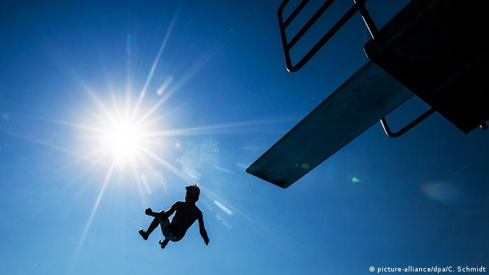 Silhouette of a kid jumping from a springboard under the sun (picture-alliance/dpa/C. Schmidt)