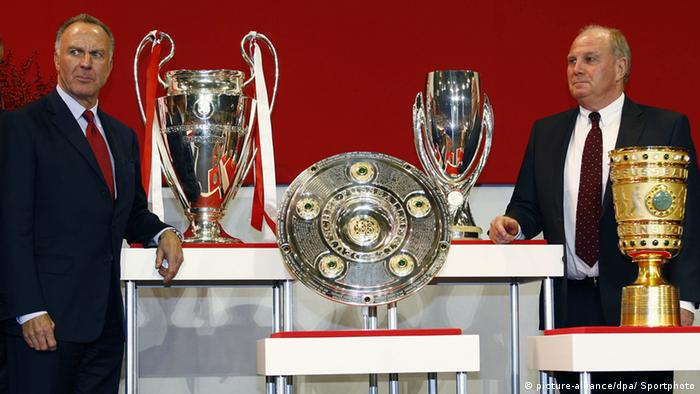 Uli Hoeness and Karl-Heinz Rummenigge standing with trophies (picture-alliance/dpa/ Sportphoto)