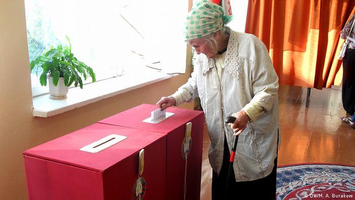Пенсионерака бросает избирательный бюллетень в урну