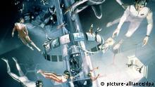Eine undatierte Illustration zeigt die Vision von zukünftigen Weltraum-Touristen, die durch die Schwerelosigkeit des Weltraums frei im Space-Hotel fliegen. Die Firma IP Space Tours GmbH stellte am Mittwoch (21.04.1999) in Bremen ihr Konzept auf einen in 15 bis 20 Jahren möglichen Weltraumtourismus vor. Dabei soll etwa das Space Hotel mit einem Durchmesser von 140 Metern in 450 Kilometern Höhe um die Erde kreisen. Die Basisstruktur soll aus Module vom Typ Spacelab bestehen und bei künstlich erzeugter Schwerkraft rund 64 Gästen einen Urlaubsort mit besonderer Aussicht auf die Erde bieten. dpa/lni (Zu dpa lni vom 21.04.1999) Copyright: picture-alliance/dpa