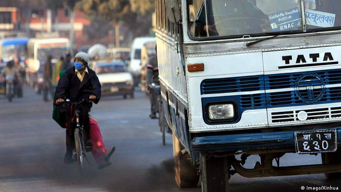 Pessoa de bicicleta usando máscara ao lado de veículo poluente