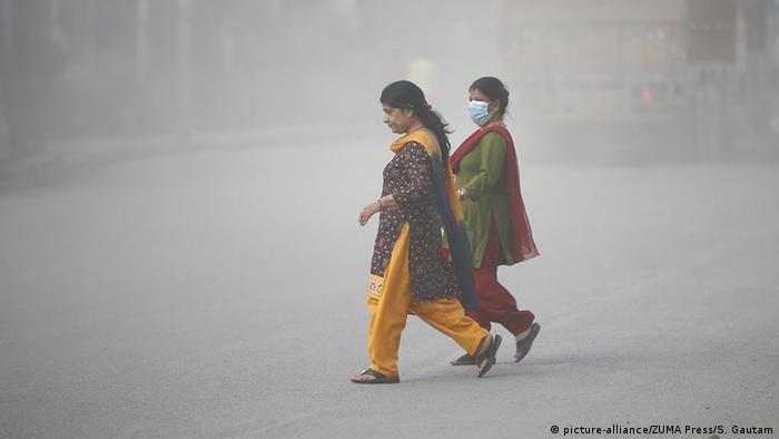 Two women walk though a smog-filled street, on is wearing a mask