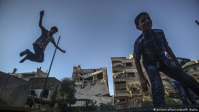 Children play on a trampoline during a cease-fire in Douma, Syria