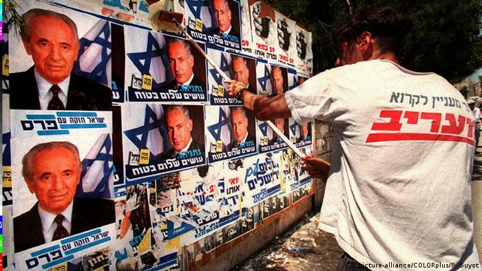 Israel Wahlkampf 1996 - rechter Aktivist überklebt Plakate von Schimon Peres (picture-alliance/COLORplus/P. Guyot)