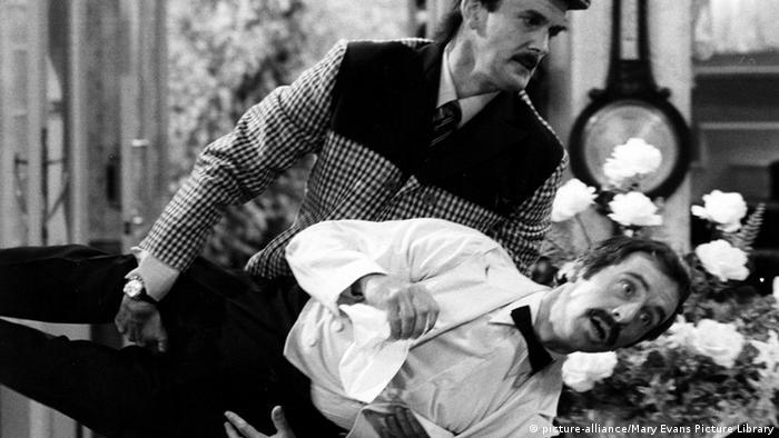 Szene aus Fawlty Towers: John Cleese als Basil Fawlty trägt Kellner Manuel