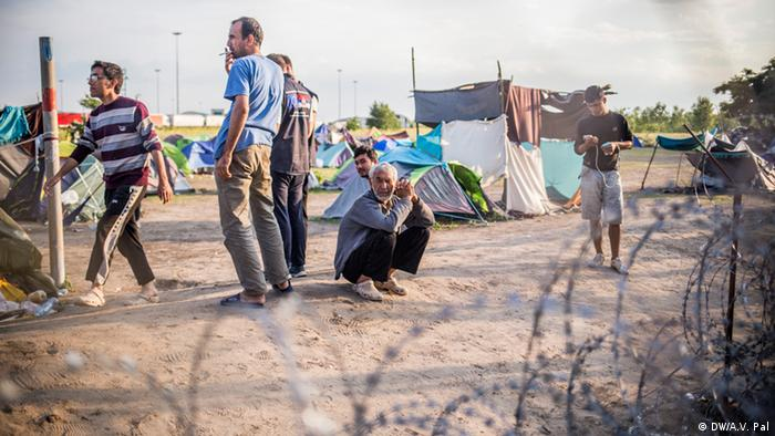 Migrants wait around in a transit camp