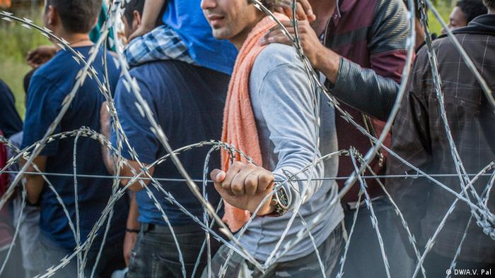 Migrants wait in line at a transit camp for food donations