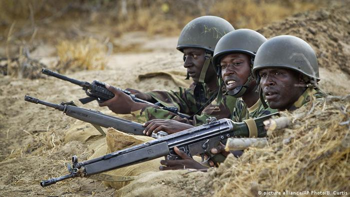 Kenyan army soldiers stand in a dugout position at their base in Tabda, inside Somalia