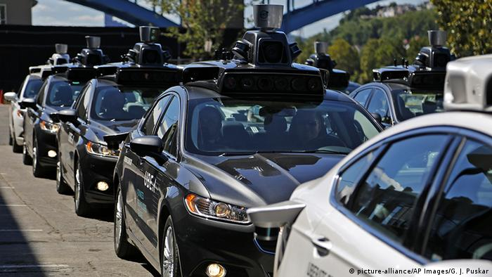 A group of self driving Uber vehicles lined up