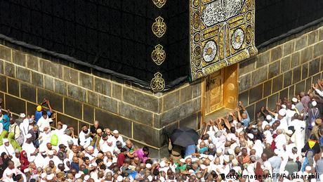 Muslim pilgrims touch the Kaaba, Islam's most important shrine