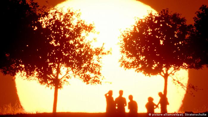 People standing in front of setting sun (Photo: picture-alliance/dpa/J. Stratenschulte)
