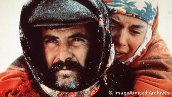 Filmszene aus Yol - Der Weg von Yilmaz Güney: Vermummter Mann, der eine Frau Huckepack trägt, Schneeszene, (Foto: Imago/United Archives)