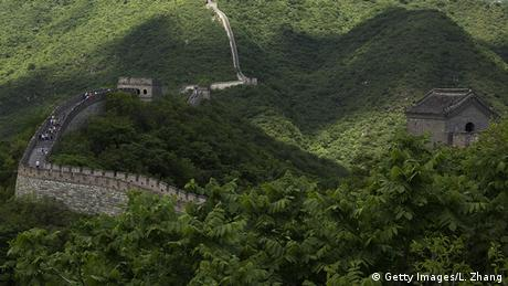 The Great Wall of China stretches through a hilly, forested landscape.