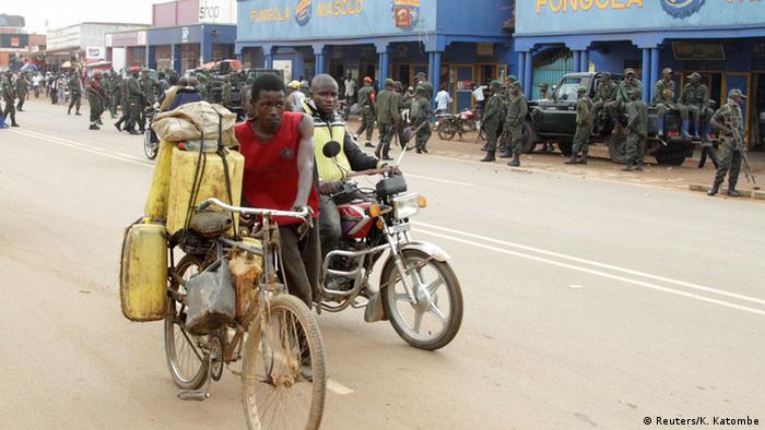 A man pushes a bicycle with goods and another rides a motorbike as Congolese soldiers look on.