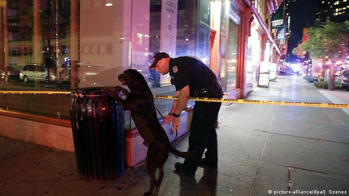 Hund mit Polizistz an Papierkorb (Foto: dpa)