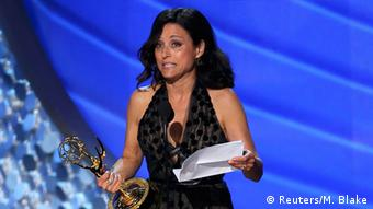 Actress Julia Louis-Dreyfus holds her Emmy in her right hand and notes in her left hand as she chokes up.