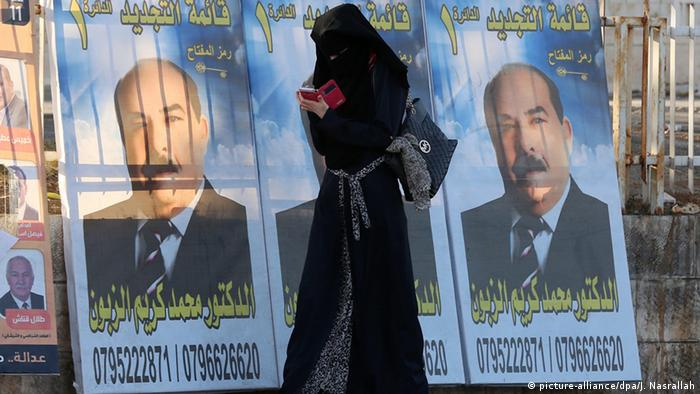 A Jordanian veiled woman uses her mobile phone as she walks next to election campaign posters in Amman, Jordan (photo: picture-alliance/dpa/J. Nasrallah)