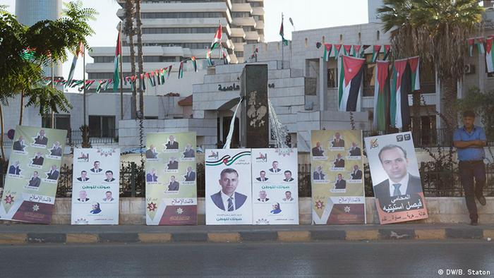 A man waits by a line of election posters in central Amman (photo: DW/B. Staton)