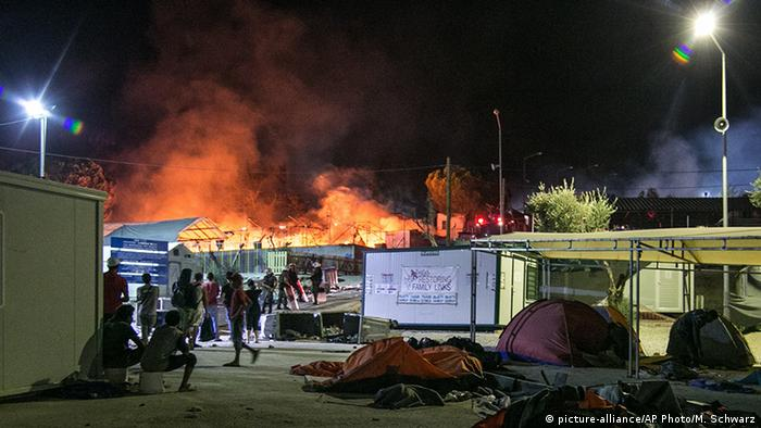 Police stand by as a fire burns at part of the Moria refugee camp in 2016 (picture-alliance/AP Photo/M. Schwarz)