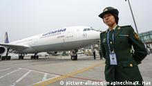 --FILE--A female police officer stands guard next to a jet plane of Lufthansa at the Qingdao Liuting International Airport in Qingdao city, east China's Shandong province, 29 March 2016. Germany's biggest airline Lufthansa and China's flagship carrier Air China have agreed a route joint venture deal that will allow them to sell each other's tickets on some routes, the companies said on Tuesday (20 September 2016). The deal caps off two years of talks that began with a signing of an accord in July 2014 and represents the closest agreement such carriers can enter short of a full-scale merger. The German airline has sought closer ties with Air China to improve its position in the world's fastest growing aviation market as European traffic slows and to stem competition from fast-growing Persian Gulf carriers on lucrative long-haul routes. Lufthansa's units Austrian Airlines and Swiss Air will also participate in the tie-up which will begin from the summer of 2017 and cover routes from China to cities including Frankfurt, Vienna and Zurich, the companies said in a statement handed out before a signing ceremony in Beijing. | © picture-alliance/Imaginechina/X. Hao