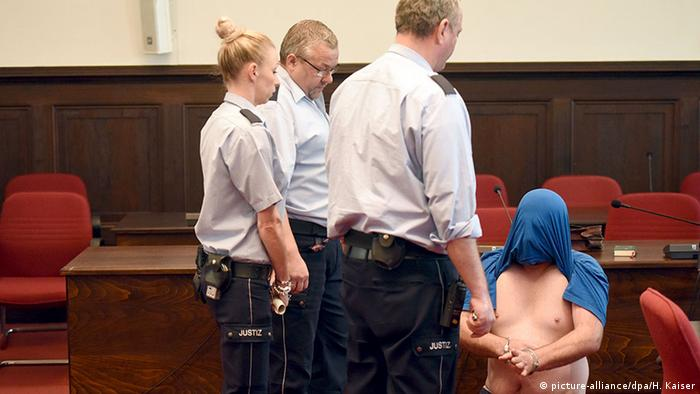 man kneels, tshirt over head, before courtroom officials Copyright: picture-alliance/dpa/H. Kaiser