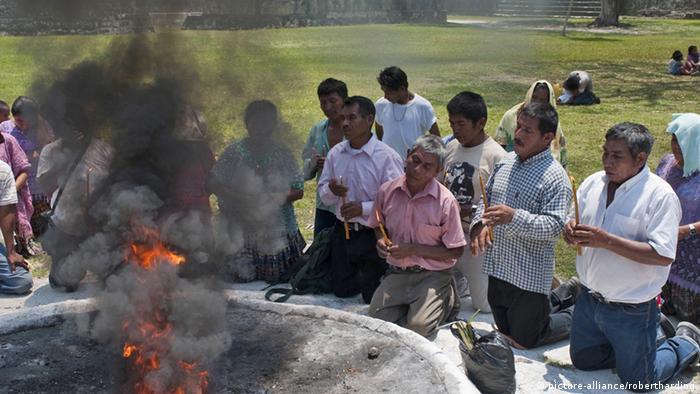 Männer knien vor einer rauchenden Schale.