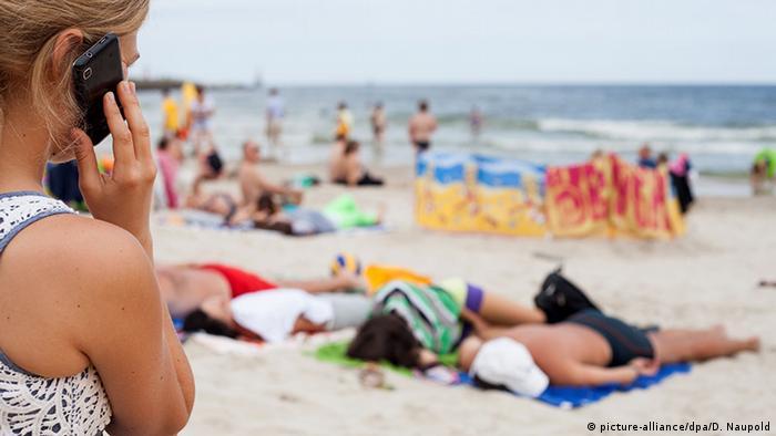 Polen Frau telefoniert am Strand