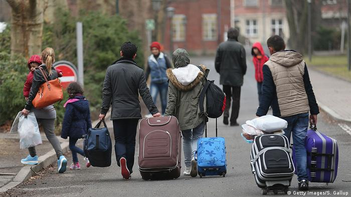 Refugees walking with suitcases