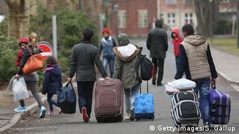 Беженцы с чемоданами на улице в Берлине