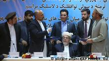 """22.09.2016 *** Amin Karim, representative of Gulbuddin Hekmatyar, right, and Afghanistan national security adviser Mohammad Hanif Atmar, third left, hold their documents after signing a peace deal, in Kabul, Afghanistan, Thursday, Sept. 22, 2016. The Afghan government has signed a draft peace deal with Hizb-i-Islami Gulbuddin, a designated """"global terrorist"""" after lengthy negotiations that could pave the way for a similar accord with the Taliban. It grants full political rights to Gulbuddin's Hezb-i-Islami party and obliges the Afghan authorities to work to have it removed from the United Nations' list of foreign terrorist organizations. (AP Photo/Rahmat Gul) 