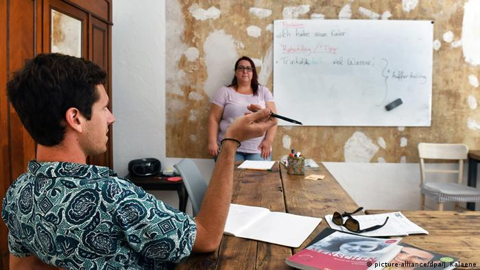 Sprachschule Sprachmafia in Berlin: Ein Schüler sitzt am Tisch, an der Tafel steht die Lehrerin Foto: Jens Kalaene/dpa
