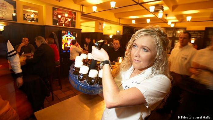 Woman serving Kölsch beer in Cologne, Germany (Privatbrauerei Gaffel)