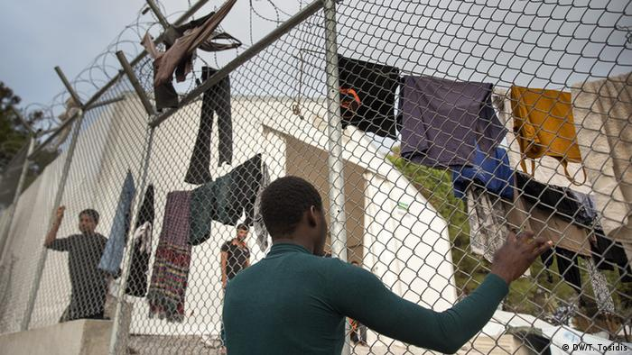 man hanging up washing on fence copyright: Dimitris Tosidis